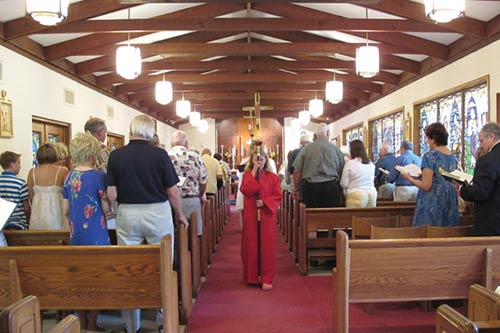Episcopal mass procession. Alter girl carring cross amid worshipers.