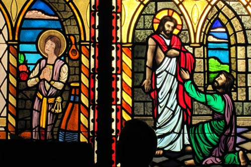 Stained glass of man on knees before Jesus. Saint looking toward heavens.